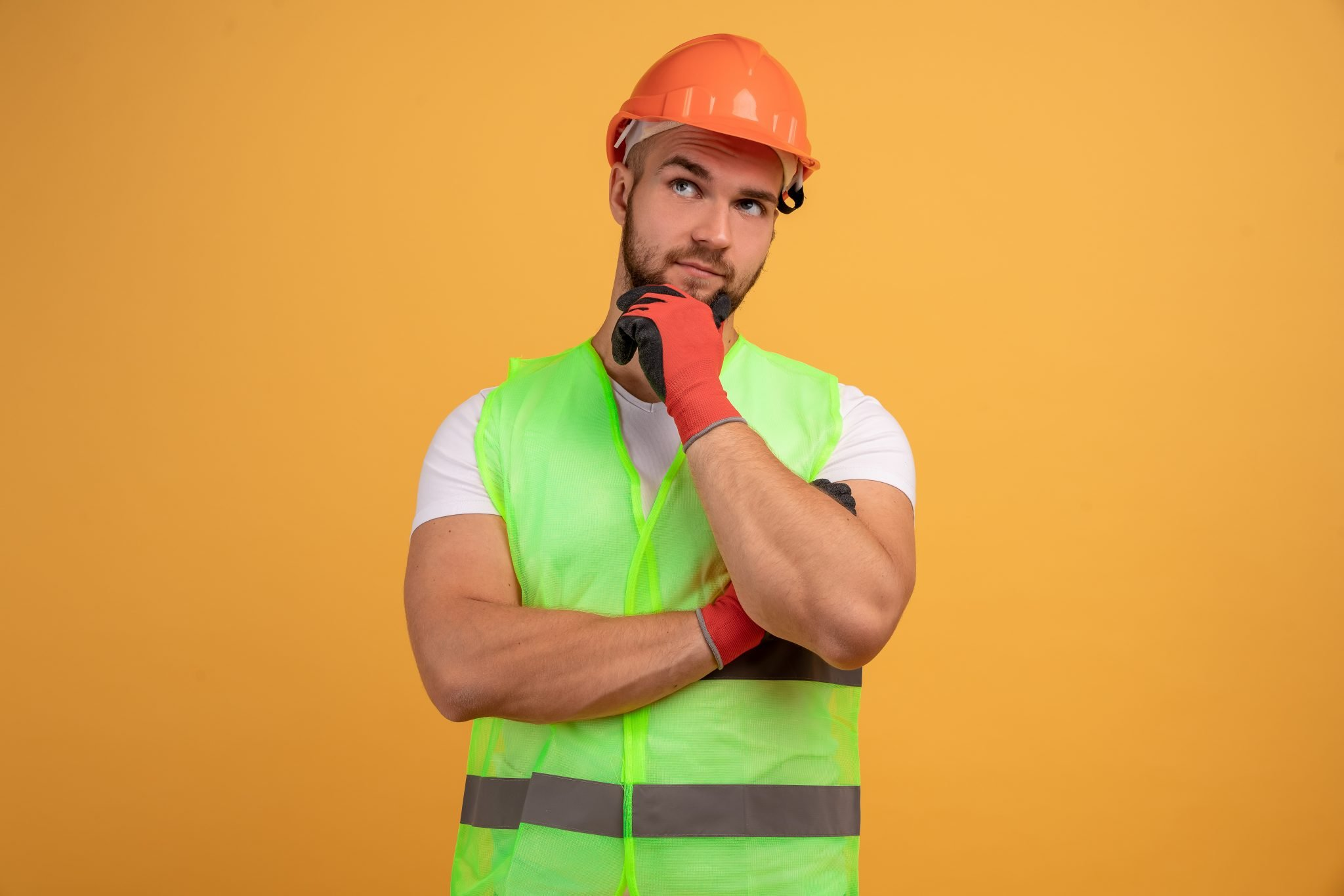 Young male constructor worker in orange hardhat thinking with one arm crossed and the other on his chin