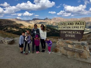 Family standing in front of Loveland Pass sign